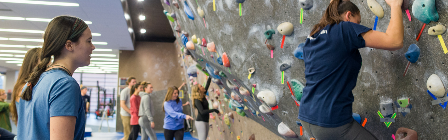 Recreation management and policy students instructing students on the climbing wall