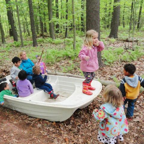group of children playing in boat in the woods