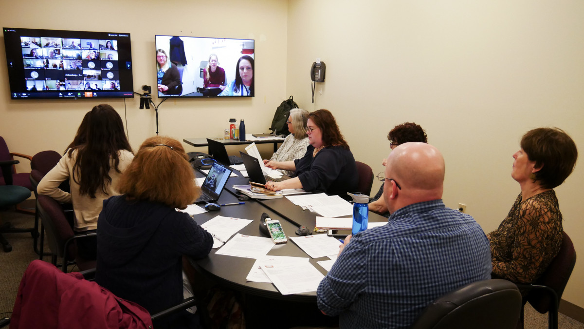 group of people gathered around a table at a meeting with screens on wall showing remote meeting participants