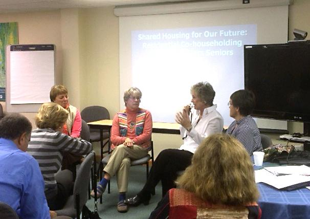 A group a people engaged in discussion during a Senior Leadership Series meeting.