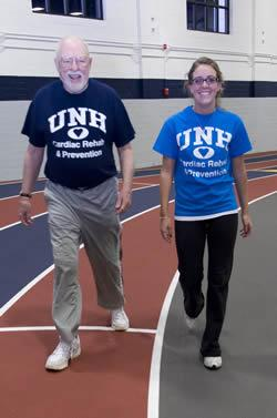 Kinesiology student walking with a man on indoor track