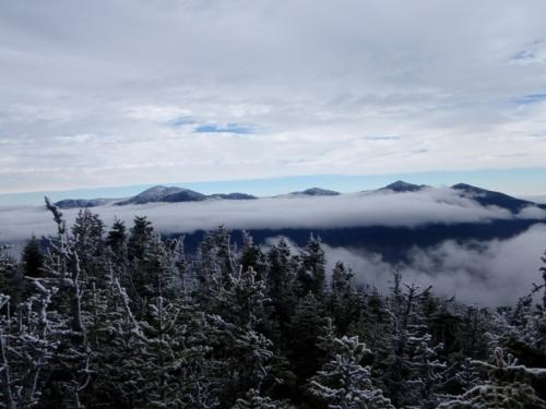 skyline with pine trees, snow, clouds, and mountains