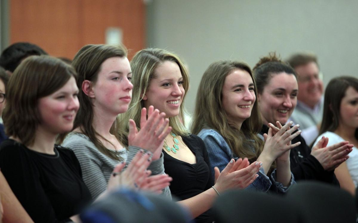 A group of young women clap in the audience at an Age of Champions event