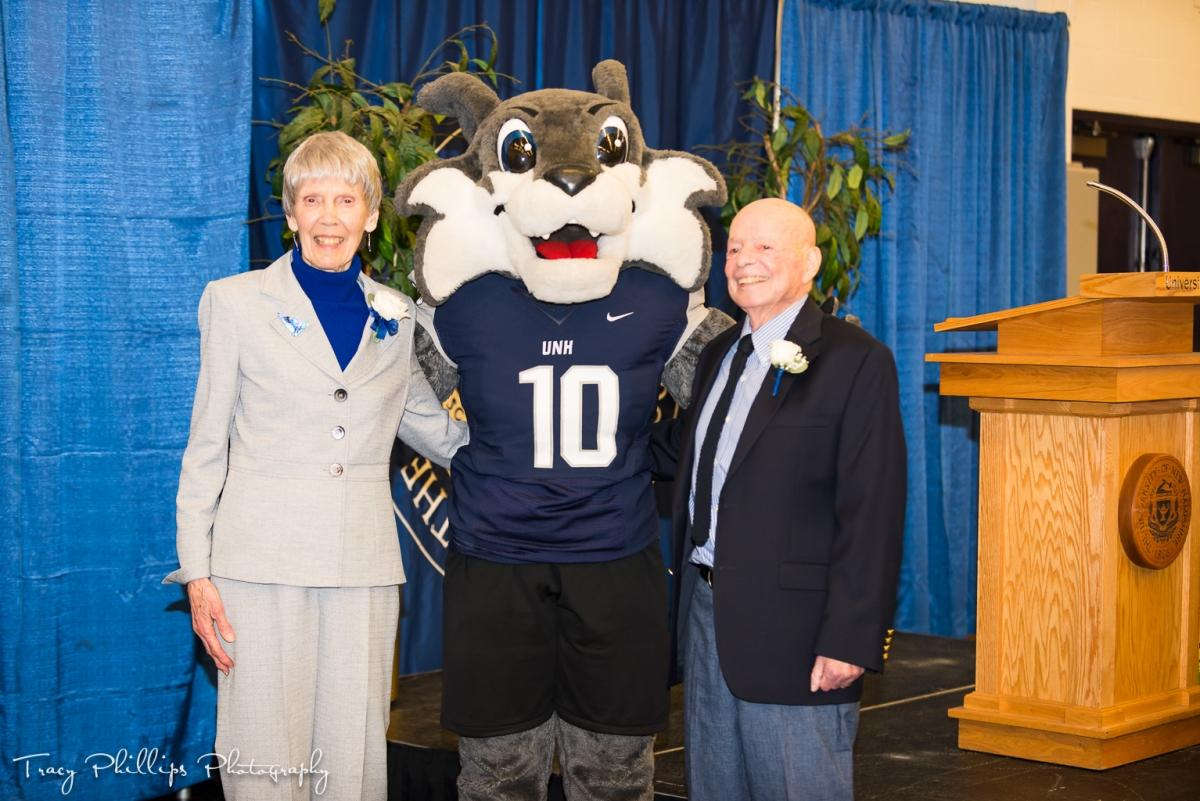 Age of Champions awardees Joyce Sheffield and Robert Kertzer stand with UNH mascot Wild E. Cat
