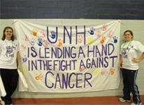 "two students standing next to ""UNH is lending a hand in the fight against cancer"" poster"